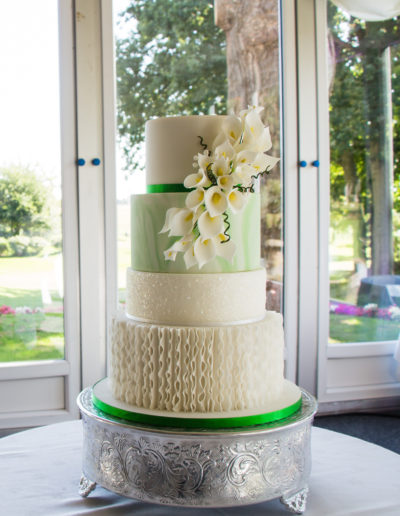 Charlotte wedding cake emerald green and white with vertical ruffles magic sparkles and cascade of sugar calla lilies Nailcote Hall Berkswell Warwickshire